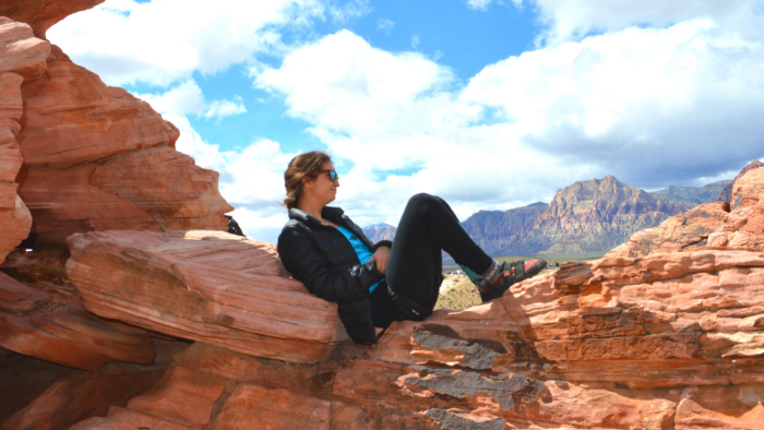 Woman sitting on rock in desert in daytime during a hike in Moab, UT.