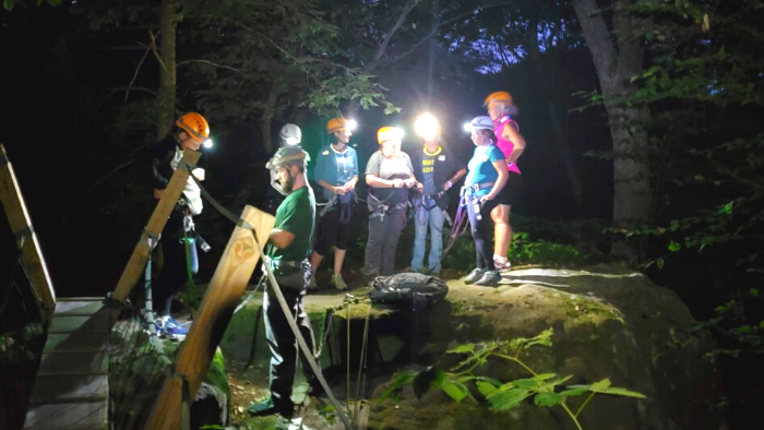 Women standing on a rock wearing headlamps at night during a rappelling trip in WV.