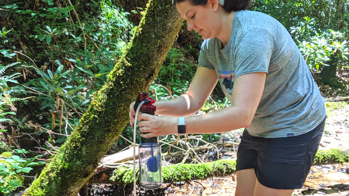 Woman using a water filtration system during a backpacking workshop in Red River Gorge.
