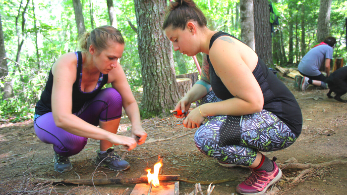 Two women kneeling down and building a fire during a survival training course in VA.