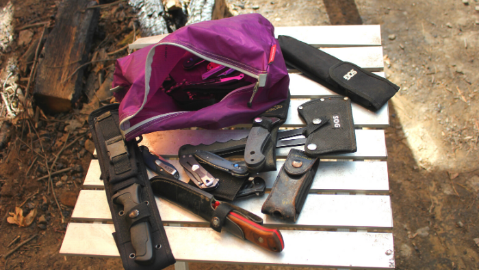 Different kinds of camping and survival knives on a table next to a purple bag.