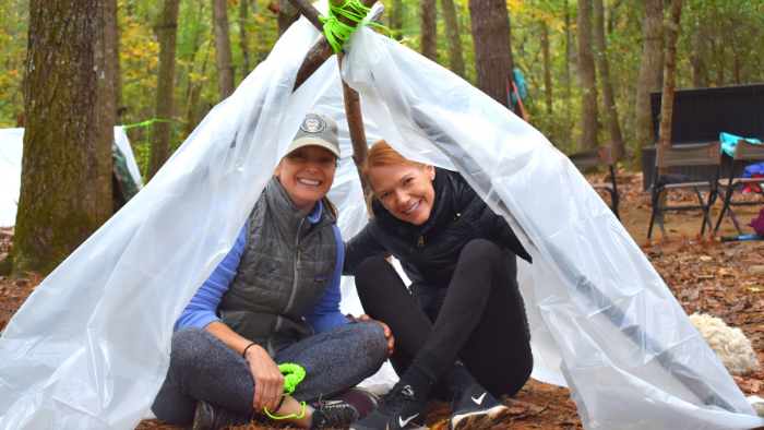 Two women sitting beneath a plastic tarp propped up with sticks during a survival training course in VA.