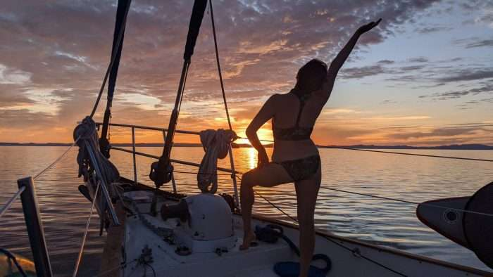Woman in swimsuit standing on bow of small cruise ship watching the sunset in Baja Mexico