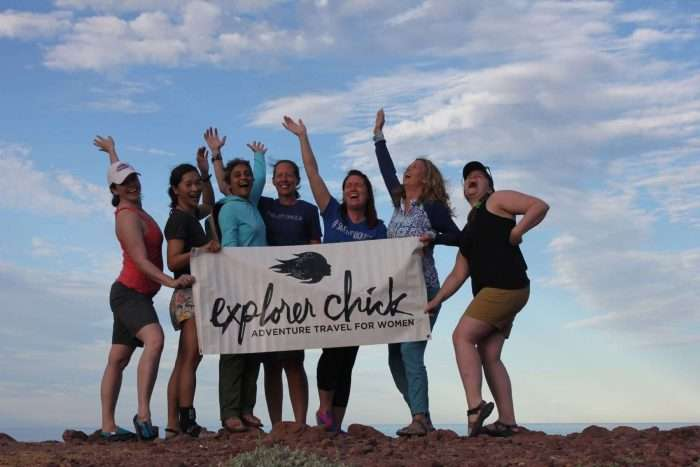 Women holding a banner from the guided tour travel company Explorer Chick.