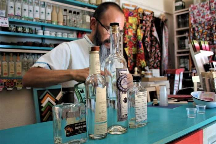 Man pouring a drink behind counter surrounded by mezcal bottles