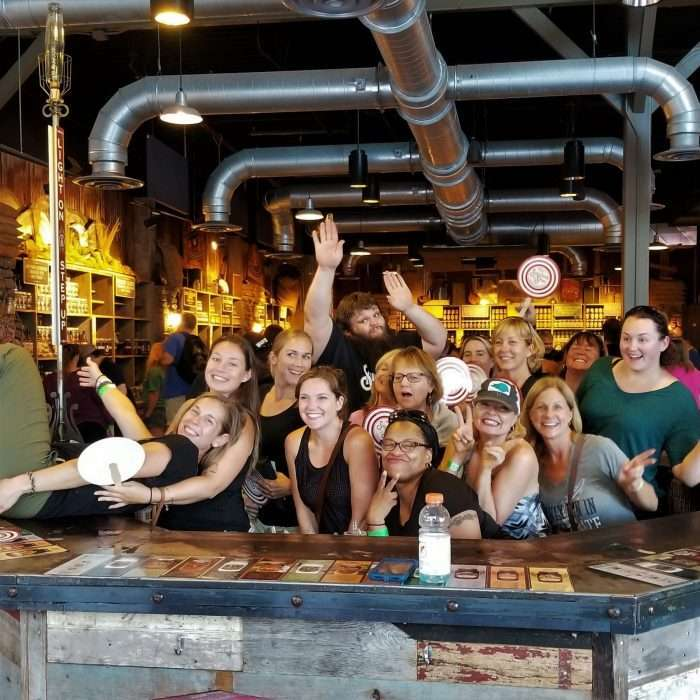 A group of women visiting a moonshine distillery, learning about moonshine recipes and flavors.