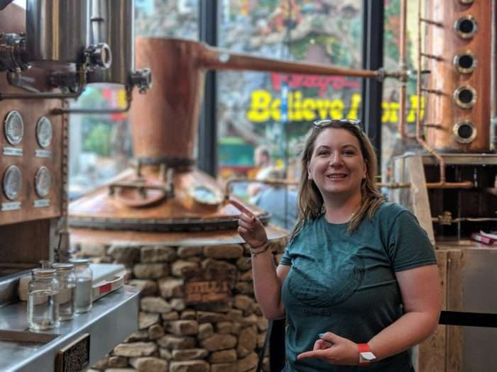 Woman pointing to a moonshine still during a trip to a distillery to learn about moonshine recipes and flavors.