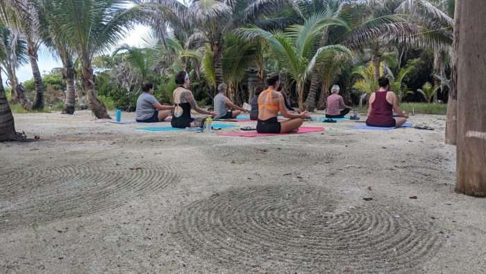 A small group of women sitting on beach doing yoga as part of a guided tour.