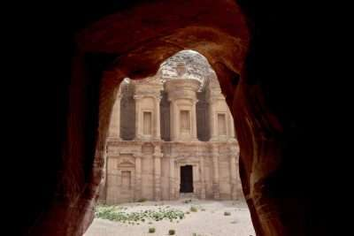 A view of the stone-carved monestary Petra through a cave opening