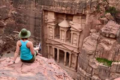 Woman sitting on rock looking at Petra in Jordan.