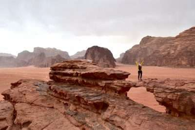 Woman standing with her arms up and looking at the desert landscape while hiking