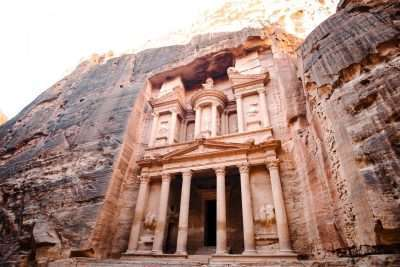 A building facade with columns carved into the side of a rock known as Petra