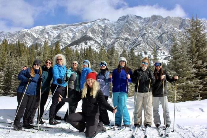 A small group of women on a guided tour, wearing skis and standing in front of a mountain and pine trees.