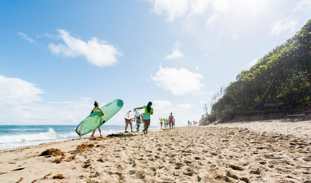 A small group of women walking on the beach carrying surfboards as part of a guided tour.