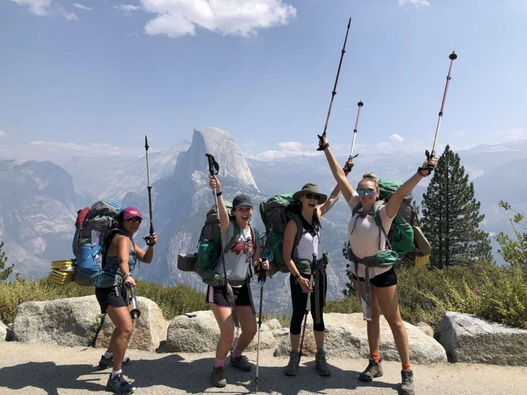 Women posing with backpacks and holding up trekking poles during a hike to Half Dome