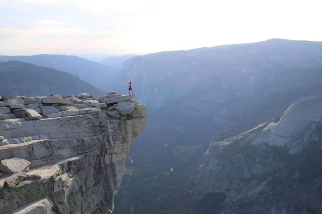 Woman standing on a rock outcropping at sunset