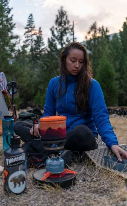 Woman cooking on a camp stove during a Yosemite Half Dome Hike and Backpacking Trip.