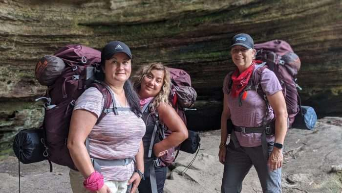 three women with purple backpacks backpacking in the red river gorge