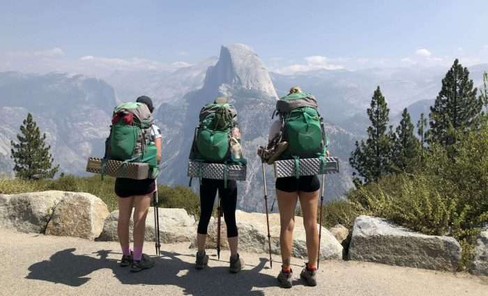 three women backpacking and viewing half dome from glacier point in yosemite