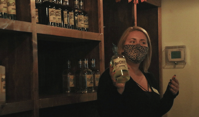 Woman demonstrating moonshine recipes and tastings during a women's hiking trip in the Smoky Mountains.