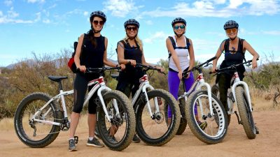 Women smiling and standing while holding fat tire bikes during a tour.