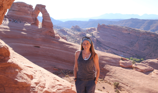 Woman posing in front of red sandstone arch wearing jewelry, a great gift idea for an outdoors-woman