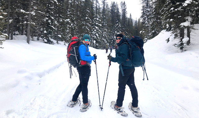Two women traveling together in Banff snow shoeing between pine trees