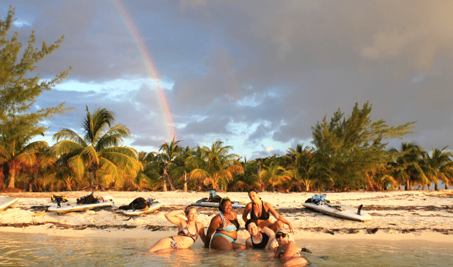 Five women traveling together posing on beach with palm trees and jet skis with a rainbow in the sky