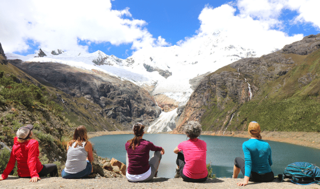 Women traveling together on Cordillera Huayhuash trek sitting by a lake and looking at mountains