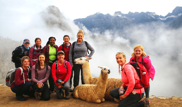 Women traveling together to Machu Picchu posing with llamas in front of foggy mountains