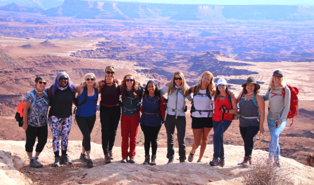 Women traveling together in Moab standing and posing in front of canyon