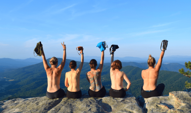 Women traveling together sitting on a rock and holding shirts up in air