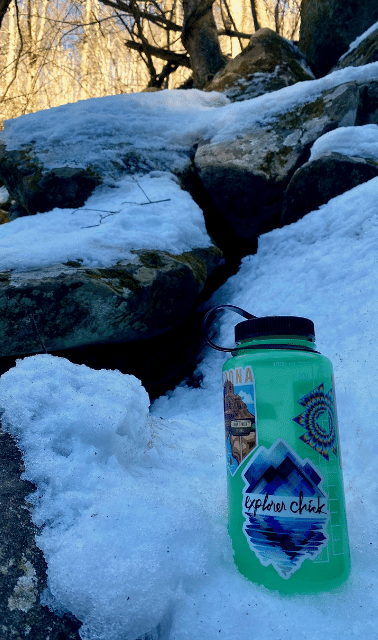 Green water bottle with Explorer Chick sticker sitting in snow and surrounded by rocks