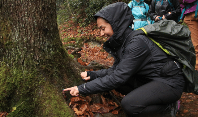 Woman in black coat leaning down and pointing to tree during a winter hike