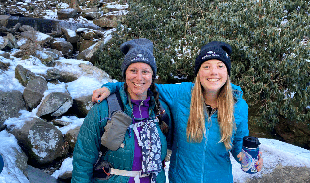 Two women in winter clothing posing in front of snowy rocks during a hiking trip