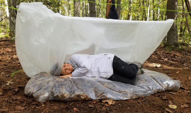 Woman lying on bed of leaves under plastic sheet while learning survival skills